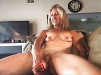 This mature slut with saggy tits looks happy while masturbating on cam
