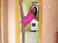 Flexible sporty brunette sexpot in bright pink swimsuit does stretching