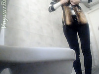 Slender white stranger girl in the toilet room shows her ass on voyeur cam